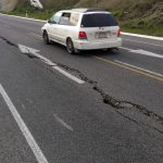 A car drives past a crack in a road after an earthquake on the outskirts of the town of Seddon in the Marlborough region, on New Zealand's South Island August 16, 2013. A magnitude 6.5 earthquake struck south of New Zealand's capital on Friday, sending panicked Wellington workers and residents into the streets, but caused little major damage just weeks after a similar size quake shook the harbourside city. REUTERS/Anthony Phelps  (NEW ZEALAND - Tags: DISASTER ENVIRONMENT TRANSPORT) - RTX12N83